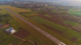 Aerial view of small airport with take off runaway and white plane flying over. 4K. stock video