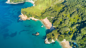 Aerial view on a small beach surrounded by rocks and forest. Coromandel, New Zealand Royalty Free Stock Photo