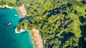 Aerial view on a small beach surrounded by rocks and forest. Coromandel, New Zealand Stock Photos
