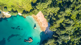 Aerial view on a small beach surrounded by rocks and forest. Coromandel, New Zealand. Coromandel peninsula is popular tourist destination in New Zealand Stock Photo