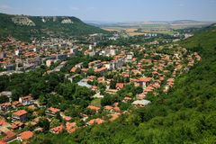 Aerial view of a small, beautiful green city with a lot of trees, situated in a deep karst gorge on a bright summer day. Town of P Stock Photography