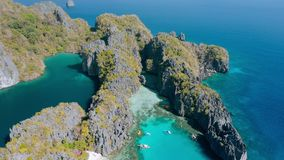 Aerial view of small and big lagoon on Miniloc Island. El-Nido, Palawan. Philippines. Limestone rock formation overgrown. With plants and blue shallow bays in stock footage