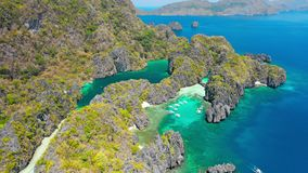 Aerial view of small and big lagoon on Miniloc Island. El-Nido, Palawan. Philippines. Limestone rock formation overgrown. With plants and blue shallow bays in stock video