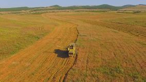 AERIAL VIEW. Small farms.Old combine harvesting. AERIAL VIEW. Old combine harvesting. Small farms. The area with hills and uplands. Uneven field. The camera stock video footage