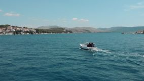 Aerial view of a small old speedboat with a man moves on the blue crystal clear sea. stock video