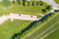 Aerial view of a small parking lot wiping rows of bushes and trees in front of the edge of an arable land. Near Wolfsburg Royalty Free Stock Image