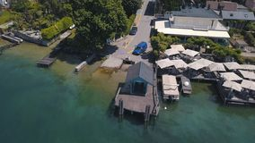 Aerial view of small pier, cafe, yachts and modern cottages near the sea in one of southern towns. Action. Summer resort. Aerial view of small pier, cafe, yachts stock images