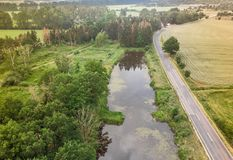 Aerial view of a small pond parallel to a country road in Saxony-Anhalt with fields and forests in the surrounding area. Made with drone Stock Photos