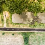 Aerial view of a small pond parallel to a country road in Saxony-Anhalt with fields and forests in the surrounding area. Made with drone Royalty Free Stock Photos