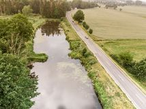 Aerial view of a small pond parallel to a country road in Saxony-Anhalt with fields and forests in the surrounding area. Made with drone Stock Photography