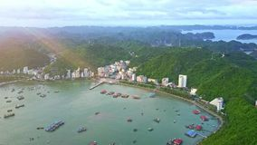 Aerial View Small Town at Hill Foot by Ocean under Sun Rays. Amazing aerial view small town located at hill foot among boundless green islands on ocean coast stock video footage