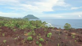 Aerial view of small tropical island with volcano and reddish frozen lava soil. Shot with drone on cloudy day with blue sky in Ternate, Indonesia, fly stock video