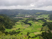 Aerial view of small village and crop fields in the valley under the mountains Royalty Free Stock Images