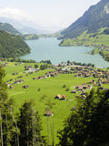 Aerial view for small village on the lake. In background Alps Stock Photos