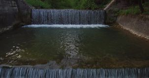 Aerial view of small waterfall on a river at the brink of forest stock footage