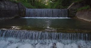 Aerial view of small waterfall on a river at the brink of forest stock video footage