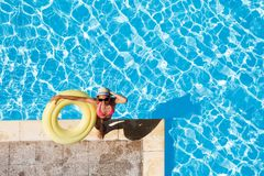 Happy woman standing at poolside with rubber ring. Aerial view of smiling attractive woman in sunglasses standing at poolside, holding yellow inflatable ring and Royalty Free Stock Photo