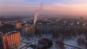 Aerial view on smoke pipe at evening winter city. Beautiful sky, aerial view, sunset dusk, winter town covered in snow stock video