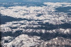 Aerial View of Snow-capped Mountain Range. An aerial view of a snow-capped mountain range showing high peaks with great detail of erosion Stock Photos