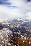 Aerial view of snow-covered mountains. Under cloudy blue sky Stock Photo