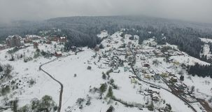 Aerial view. Snow covered village on a hilly terrain stock footage