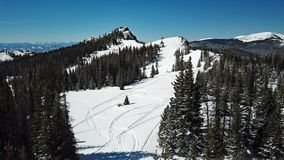 Drone shot of snowy mountain snowmobile tracks royalty free stock photography