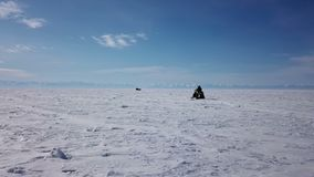 Aerial view snowmobiles ride on the frozen Lake Baikal in winter stock video