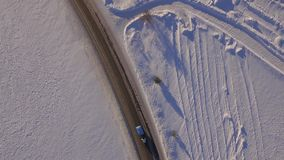 Aerial view of snowy fields and road. SUV driving on winter roads through the snowy field. Aerial view of the car stock footage