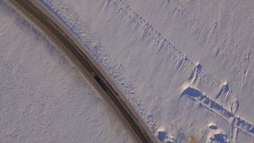 Aerial view of snowy fields and road. SUV driving on winter roads through the snowy field. Aerial view of the car stock video