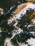 Aerial view of snowy forest with a road. Captured from above with a drone Royalty Free Stock Photography