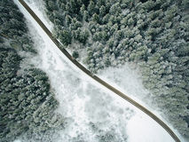 Aerial view of snowy forest with a road. Royalty Free Stock Photo