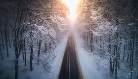 Aerial view of snowy forest with a road at sunset. Captured from above with a drone. Carpathians, Romania stock images