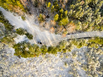 Aerial view of snowy forest in sunny winter day. With country road. drone photography Stock Photo