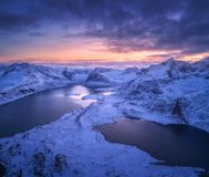 Aerial view of snowy mountains, sea, colorful cloudy sky at night. In Lofoten islands, Norway. Winter landscape with snow covered rocks and seacoast and sunset royalty free stock images