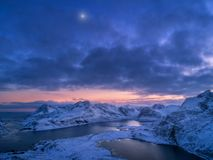 Aerial view of snowy mountains, sea, colorful cloudy sky at night. In Lofoten islands, Norway. Winter landscape with snow covered rocks and seacoast and sunset stock photo