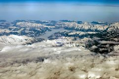 Aerial view of snowy mountains in winter. Flying above the clouds stock images