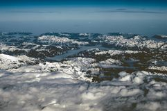 Aerial view of snowy mountains in winter. Flying at sunset above the clouds stock photos