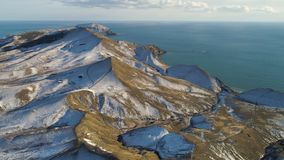 Aerial view of snowy rocks, blue sea, on cloudy sky background. Shot. Snow-covered hills in Iceland by the sea in a royalty free stock image
