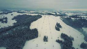 Aerial view of a snow covered alpine skiing slopes in winter. Ski resort in southern Poland, the Tatra mountains. Aerial view of a snowy ski resort stock video footage