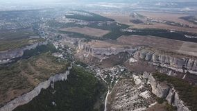 Aerial View: a span in the middle of a canyon, on one side of the cliff, on the other side of the forest. In the middle stock footage