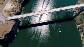 Aerial view of a speed boat passing under a bridge stock footage