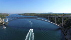 Aerial view of speedboats driving under bridge over dalmatian canal, Croatia. Aerial view of speedboats passing under bridge over forested green dalmatian canal stock video