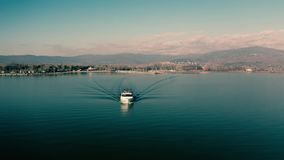 Aerial view of speeding motor boat and distant mountainous shore stock footage