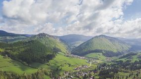 Aerial view of spring country with fresh green colors. Flight above rural country village with clouds moving over fresh green colored landscape in spring. Hyper stock video footage