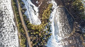 Aerial view of spring rural road in yellow pine forest with melting ice lake stock images