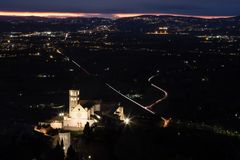 Aerial view of St. Francis papal church in Assisi at night, with. City lights filling the valley and distant dusk colors in the sky stock photography