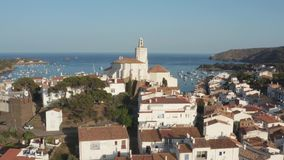 Aerial view of St. Mary church in Cadaques town. Drone view of resort coastal town Cadaques with church of St. Mary among white houses on background of beautiful stock video