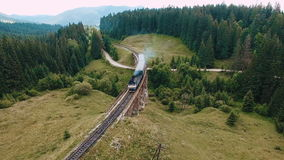 Aerial view of steam train crossing bridge stock video footage