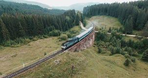 Aerial view of steam train crossing bridge stock video footage