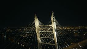 Aerial view steel cable stayed bridge and night car traffic in modern city. Of the future. Car driving on modern night highway bridge over city river drone view stock video footage